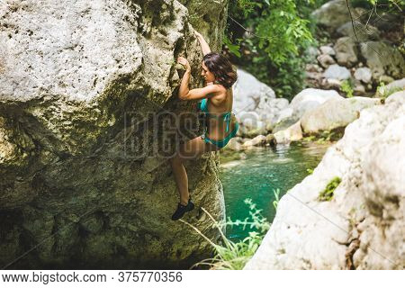 A Woman In A Swimsuit Climbs A Cliff Above The Water, Climbing Over A Mountain River, Bouldering In