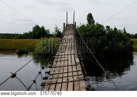 Suspended Wooden Bridge Over A River. Old Suspended Wooden Bridge In The Summer.
