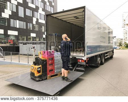 Delivery Man Talking On A Mobile Phone As Beverages Are Unloaded With A Forklift On A Tailgate Loade