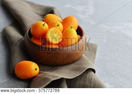 Wooden Bowl Full Of Fresh Kumquat Fruits On Brown Linen Napkin On Grey Concrete Background. Copy Spa