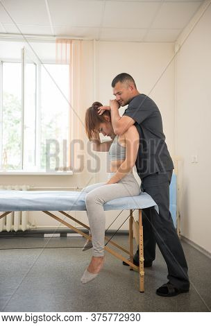 Young Woman Sitting On The Couch And Having Osteopathic Treatment In The Clinic - The Doctor Working