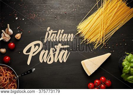 Top View Of Tasty Bolognese Pasta In Frying Pan Near Ingredients On Black Wooden Background, Italian