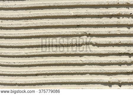 Background Of Old Tile Adhesive On Wall Being Repaired. Abstract Pattern Of Notched Trowel. High Res