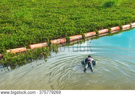 Hunter Fisherman With A Speargun On A Life Ring Looks Under The Water In Search Of Fish In The Eveni