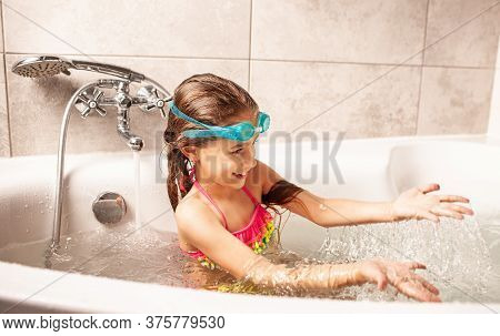 Emotional Funny Caucasian Girl Joyfully Plays With Water While Bathing In The Bathroom. Concept Of E