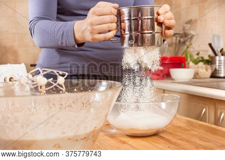 Flour Sifted Through A Strainer Into A Bowl. A Woman Holds A Strainer And Sifts Flour Into A Bowl. A