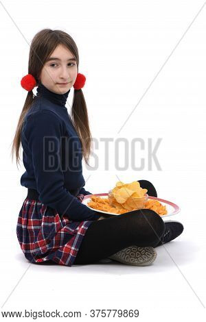 Pre-adolescent Girl Holding Plate Is Full Of Potato Chips. Isolated On White Background. High Resolu