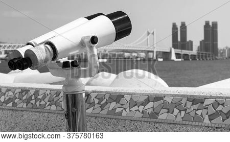 Binocular Telescope On A Rotating Base Mounted On An Outdoor Touristic Viewpoint With Blurred Citysc