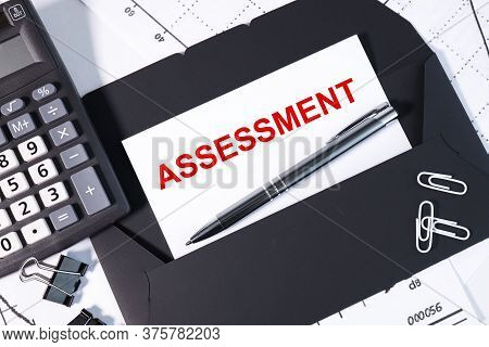 Text Note - Assessment, Business Concept On A White Sheet, On A Black Envelope Near The Financial Ch