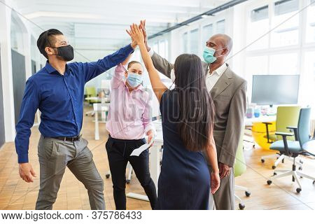 Multicultural business team with mouthguard giving high five for motivation and team building