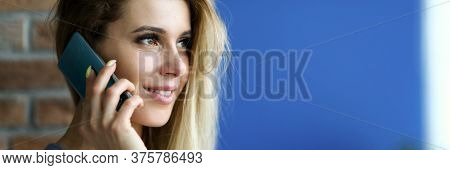 Portrait Of Smiling Charming Young Woman Talking On Mobile Phone And Looking Away. Blonde Lady Holdi