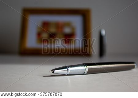 Pen On Beautiful White Fon On Warm Sunlight. Wooden Picture Frame And Cap In The Background.