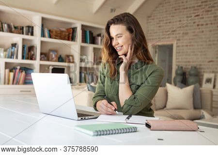 Caucasian woman spending time at home, using her laptop, working from home. Lifestyle at home isolating, social distancing in quarantine lockdown during coronavirus covid 19 pandemic.