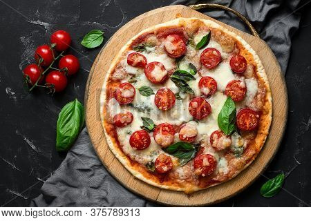 Traditional Italian Pizza Margherita On A Wooden Cutting Board, Black Stone Background. Pizza With T