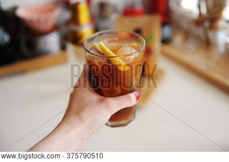 Espresso Tonic With Lemon Slice In Bid Glass With Ice In Female Hand Close Up
