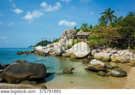 Tropical island paradise, Small bay among rocks with turquoise clear sea water, hurt behind big boulders. Romantic hidden vacation place. Koh Tao island popular destination travel holidays in Thailand