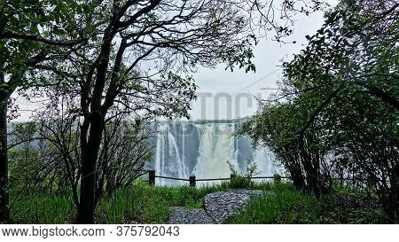 Victoria Falls, Zimbabwe. In The Foreground Is Green Grass, Trees, A Path, A Fence In Front Of The P