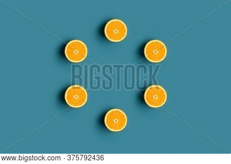 Pattern Circle With Fresh Orange Fruit At Blue Background. Concept Of Vegan Fresh Raw Food. Top View