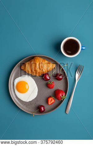 Minimal Breakfast At Blue Background. Fried Egg, Croissant, Berries And Cup Of Coffee At Blue Backdr
