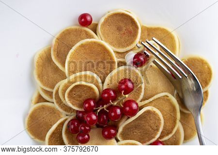 Closeup Of Tiny Pancake Cereal On White Plate Served With Red Currant Berries And Fork. Trendy Break
