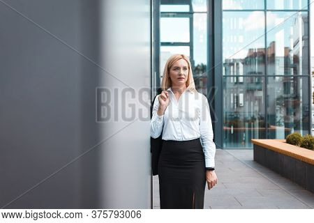Tired Female Office Worker After Hard Working Day Stands Holding A Jacket On His Shoulder