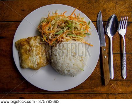 Grilled Barracuda With Rice And Vegetables On Plate