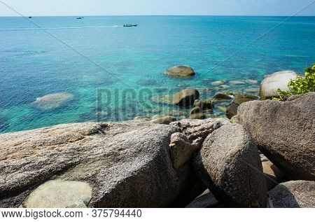 Tropical island coast with turquoise clear water, rocky bottom, boulders, boat in open sea. Koh Tao island popular destination for travel holidays in Thailand