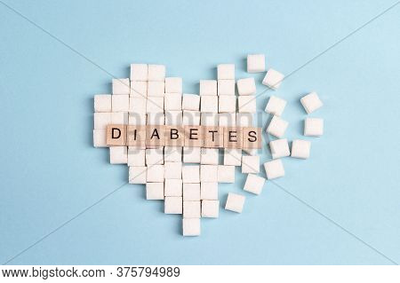 Broken Heart Made Of Sugar Cubes With Inscription Diabetes On A Blue Background. World Diabetes Day