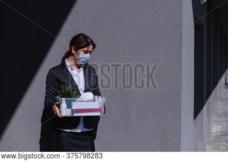 Unhappy Unemployed Woman In A Protective Mask Is Standing With A Box Of Personal Belongings Against
