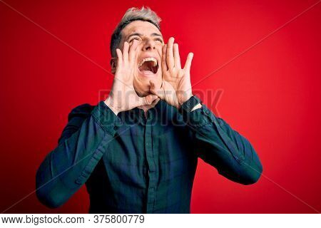 Young handsome modern man wearing elegant green shirt over red isolated background Shouting angry out loud with hands over mouth