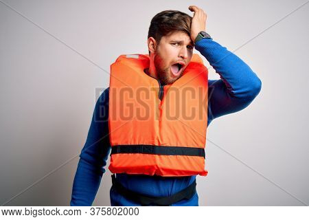 Young blond tourist man with beard and blue eyes wearing lifejacket over white background surprised with hand on head for mistake, remember error. Forgot, bad memory concept.