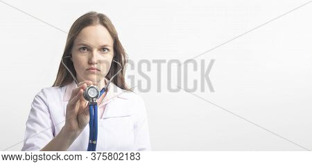 Close Up Portrait Of Young Caucasian Doctor Woman With Stethoscope Using In Direction To Camera In C