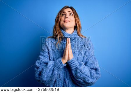 Young beautiful brunette woman wearing casual turtleneck sweater over blue background begging and praying with hands together with hope expression on face very emotional and worried. Begging.