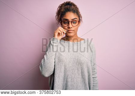 Young beautiful african american girl wearing sweater and glasses over pink background mouth and lips shut as zip with fingers. Secret and silent, taboo talking