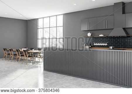 Corner Of Modern Kitchen With Gray Walls, Concrete Floor, Gray And Wooden Island And Long Dining Tab