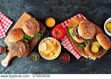 Summer Bbq Hamburger Table Scene. Overhead View On A Dark Slate Background.