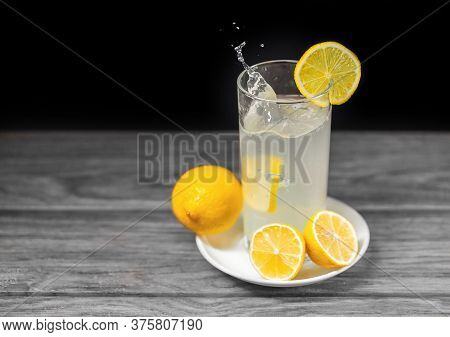 A Glass Of Lemonade With A Yellow Lemon Falling Into The Glass And Lemon Slices On The Plate With Gr