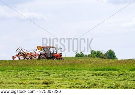 Skutech, Czech Republic, 4 June 2020: A Small Tractor With A Rotary Rake Rakes Freshly Cut Grass In