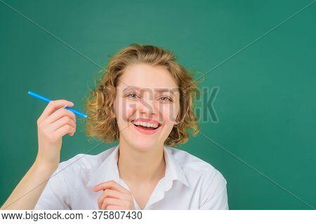 Smiling Teacher Holds Pencil. Teacher In Classroom. School Subjects. Back To School. Portrait Of Fem