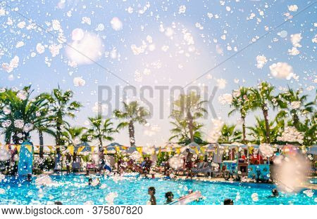 Foam Pool Party, Bubbles Blower And Pool With People Swimmng, Dancing, Relaxing And Having Fun Again