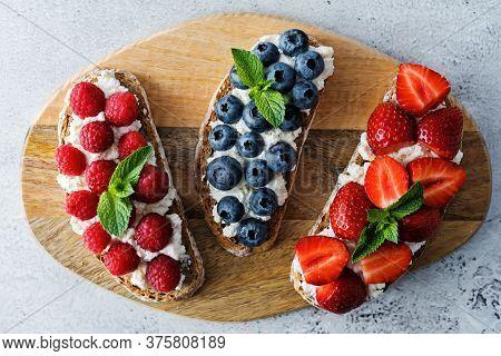 Fresh Breakfast With Blueberry, Strawberry And Raspberry Ricotta Rye Sandwiches