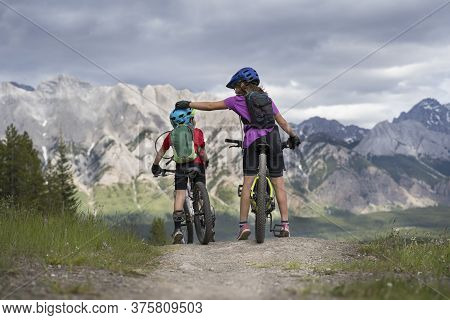 A Big Sister Is Comforting A Little Brother On A Family Mountain Bike Ride In Kananaskis Alberta Can