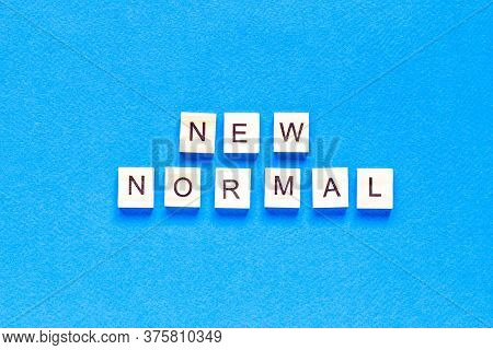 New Normal Word On Wooden Alphabet Cube. New Normal Concept. Top View, Flat Layout.