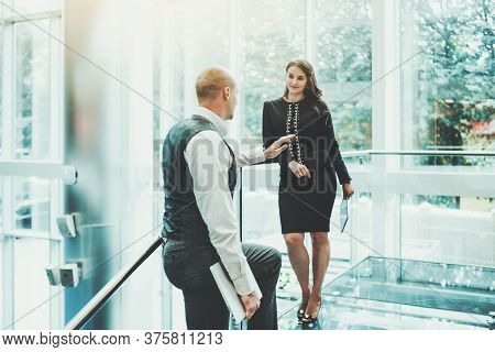 Two Entrepreneurs Having A Conversation On The Top Of A Modern Glass Office Stairway: A Man With A L
