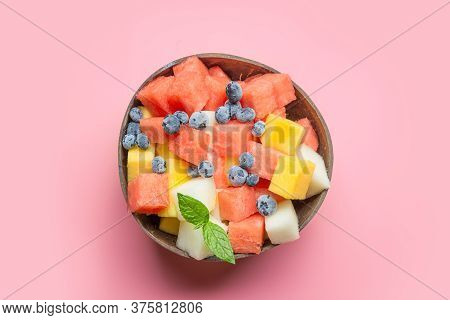 Fruits Salad Of Melon, Watermelon In Coconut Bowl On Pink Background. Healthy Breakfast. View From A