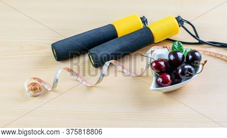 Jump Rope, Dosing Tape And Heap Of Fresh Ripe Cherries On The Wooden Table. Healthy Lifestyle Concep