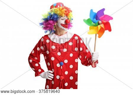 Funny clown blowing a pinwheel toy isolated on white background