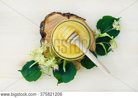 Top View, Jar Of Linden Honey, Dipper, Lime Flowers, Leaves On A Light Wooden Background, Close Up