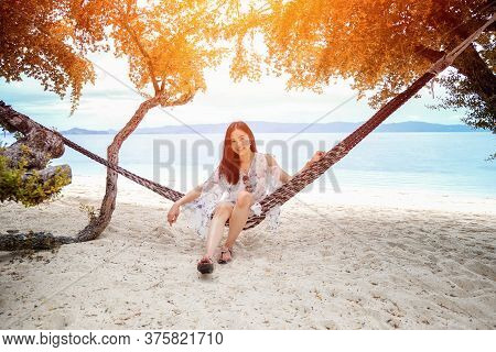 Beautiful Woman Sitting On A Swing On The Beach  In Koh Phangan, Thailand