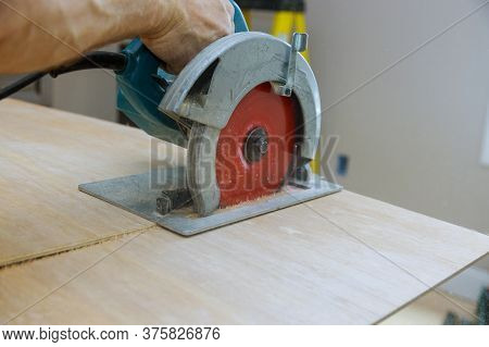 Works Sawing Plywood With Electric Circular Saw At Cutting Wooden Plywood